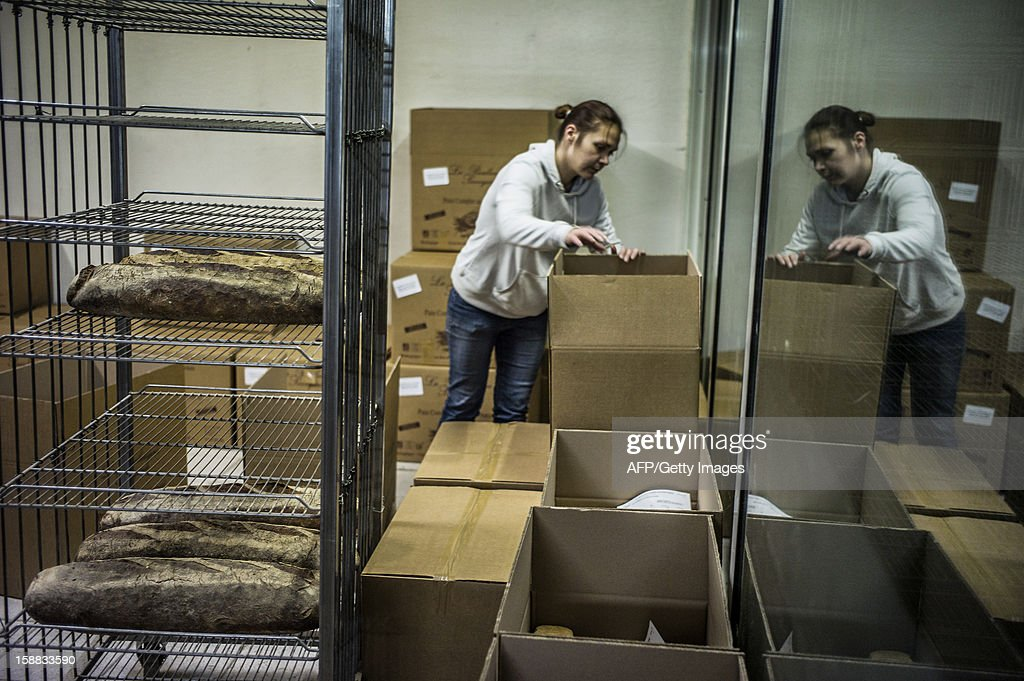 A baker stores bread for delivery, on December 27, 2012 in a bakery of Ecole en Bauges, French Alps. AFP PHOTO / JEFF PACHOUD