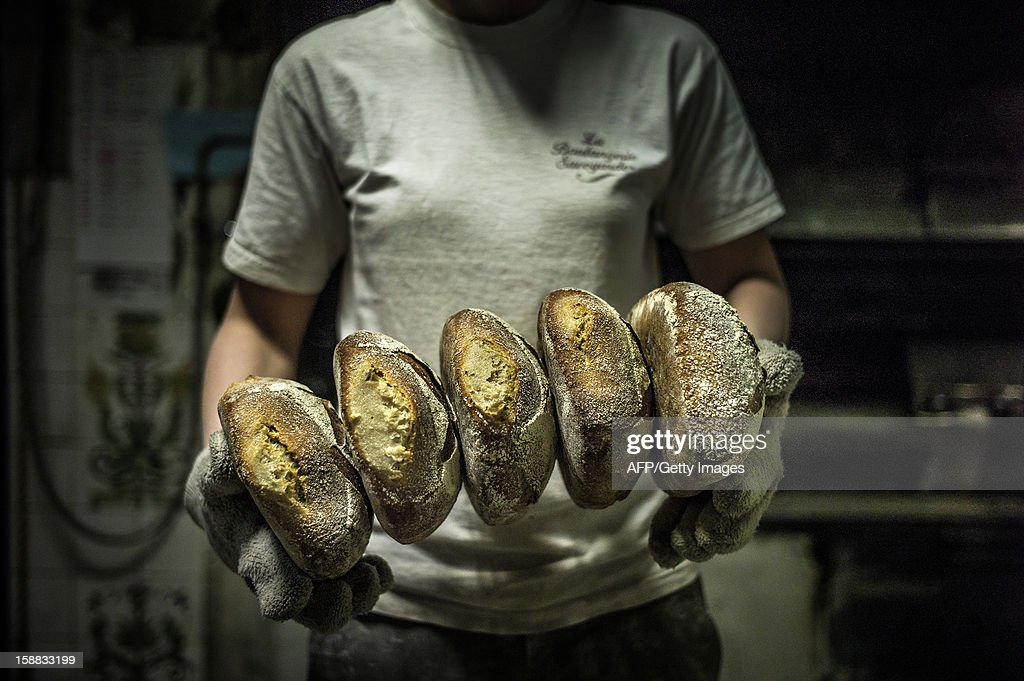 A baker stores breads after baking, on December 27, 2012 in a bakery of Ecole en Bauges, French Alps. AFP PHOTO / JEFF PACHOUD