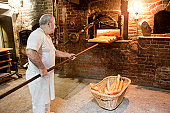 Baker taking bread out of oven in antique bakery