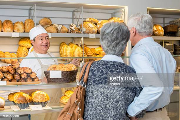 Baker talking to customers at the bakery