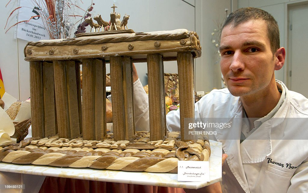 Baker Thomas Borchardt presents his cake for the baker guild theme 'Fall of the Berlin Wall', in Halle, eastern Germany, on January 14, 2013.