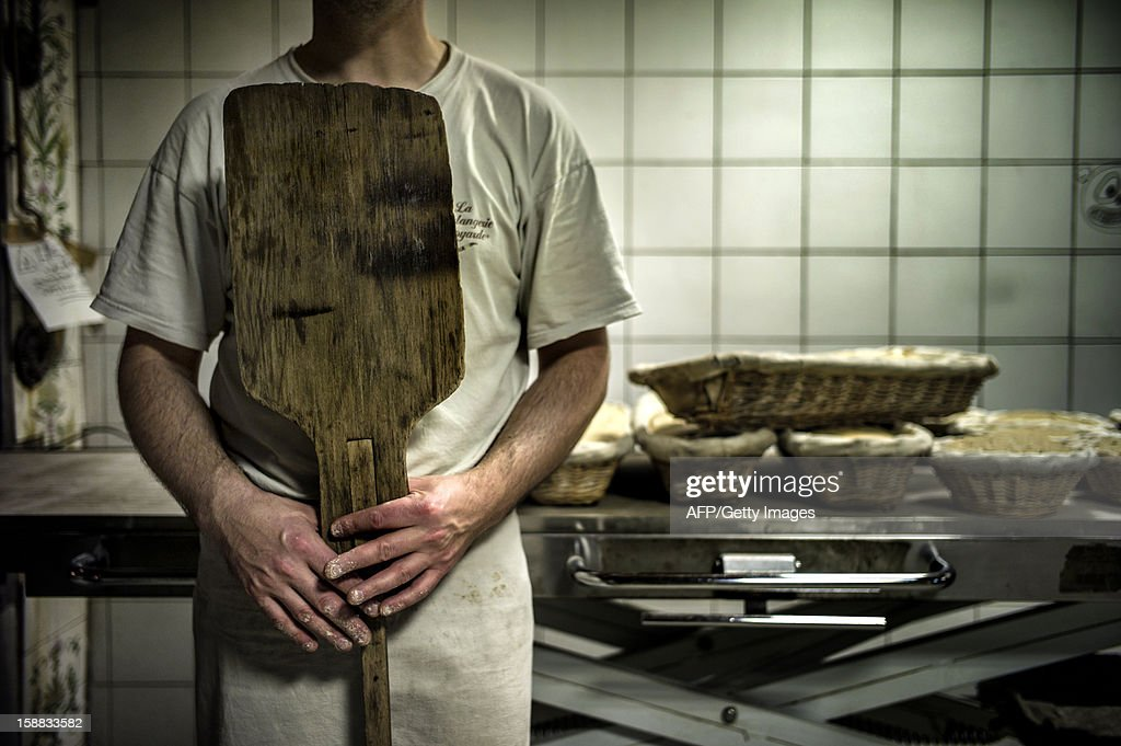 A baker waits in front of the bread oven, on December 27, 2012 in a bakery of Ecole en Bauges, French Alps. AFP PHOTO / JEFF PACHOUD