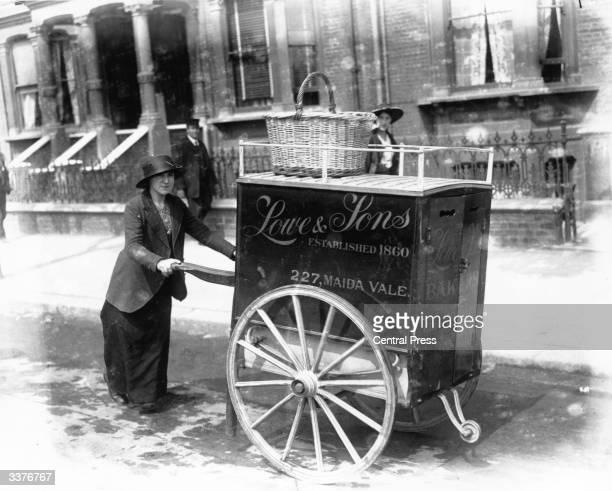 A baker wheeling her bread barrow through a London street