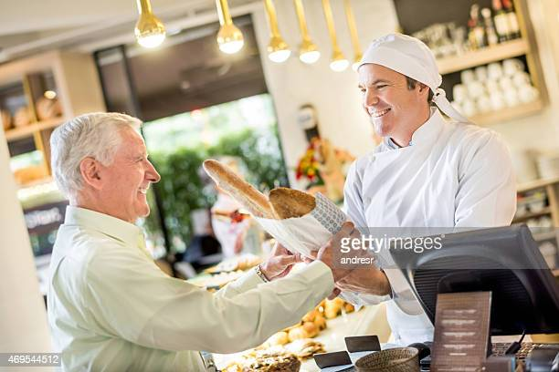 Baker working at the bakery helping some customer