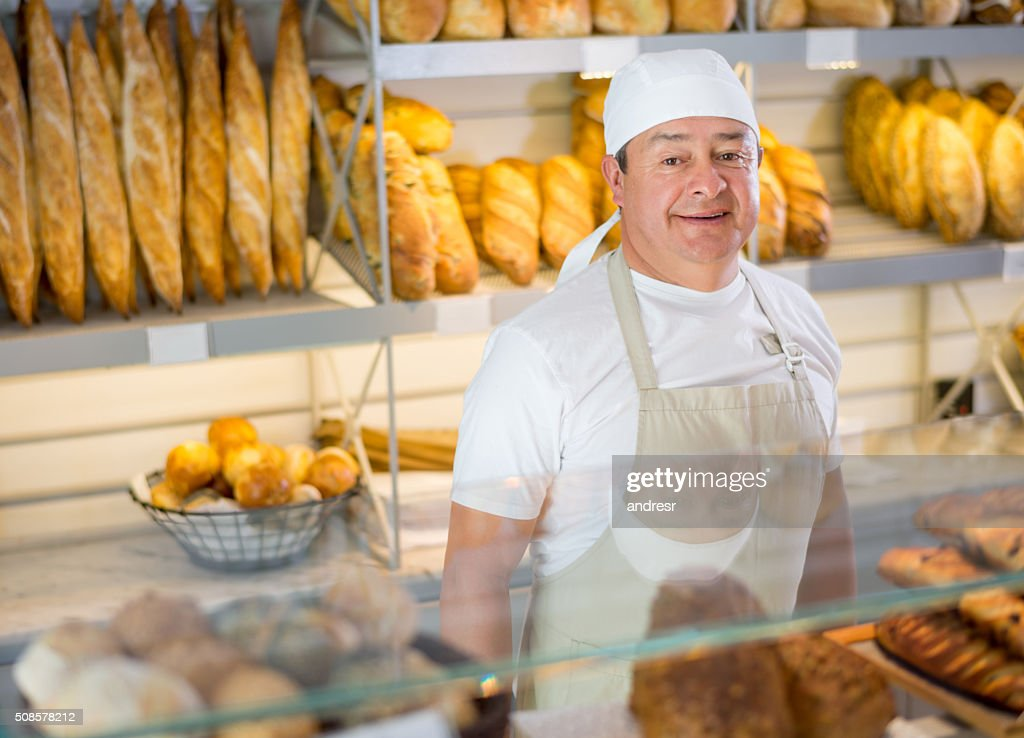 Baker working at the bakery : Stock Photo