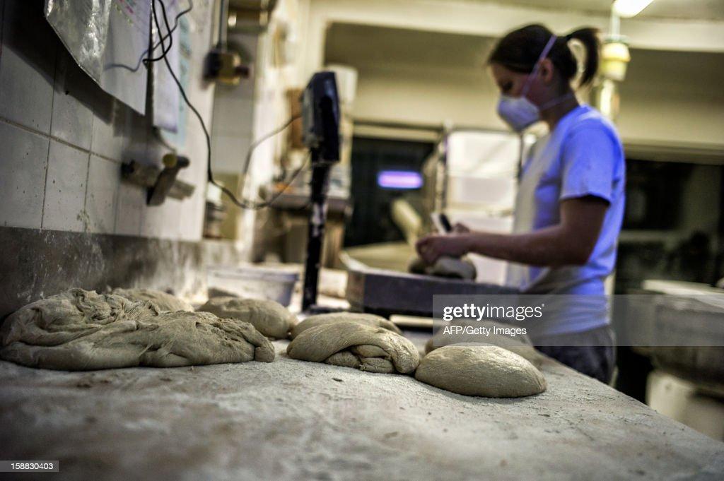 A baker works bread dough on December 27, 2012 in 'La Boulangerie Savoyarde' in Ecole-en-Bauges, French Alps.