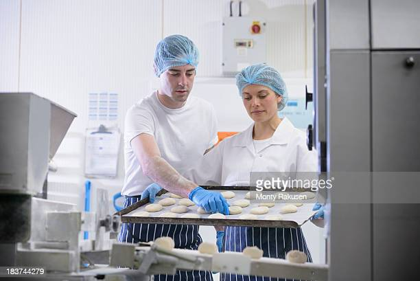 Bakers arranging dough on tray
