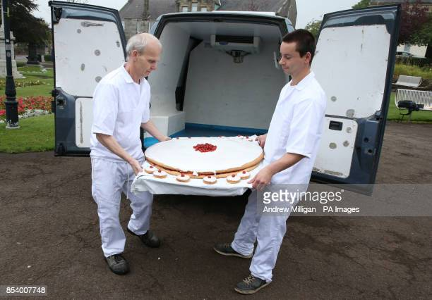 Bakers Brian Clark and Jonathan Lightbody with what is claimed to be the world's largest ever empire biscuit as it is unveiled in Market Square...