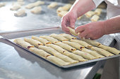 baker's female hands spread dough rolls on a tray for baking