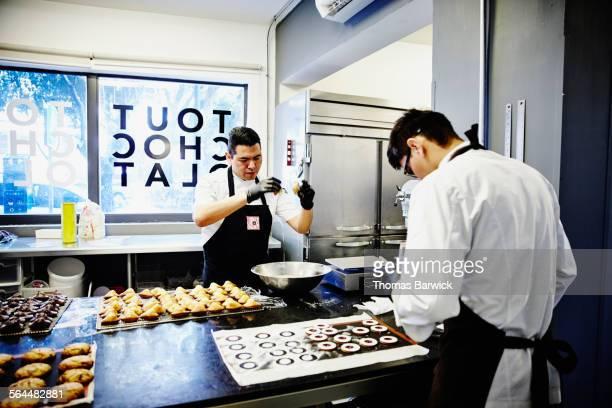 Bakers finishing freshly baked goods in kitchen