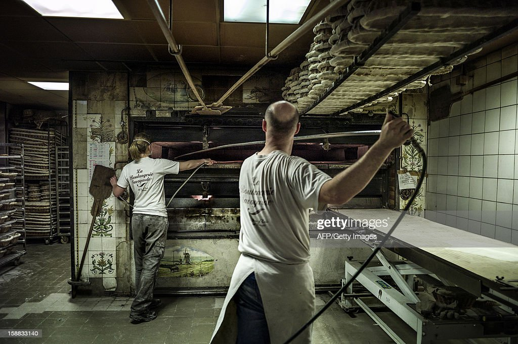 Bakers prepare the bread oven, on December 27, 2012 in a bakery of Ecole en Bauges, French Alps.