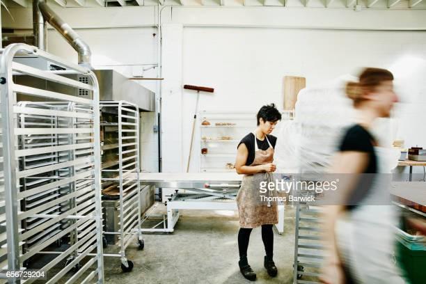 Bakers preparing bread for oven in bakery