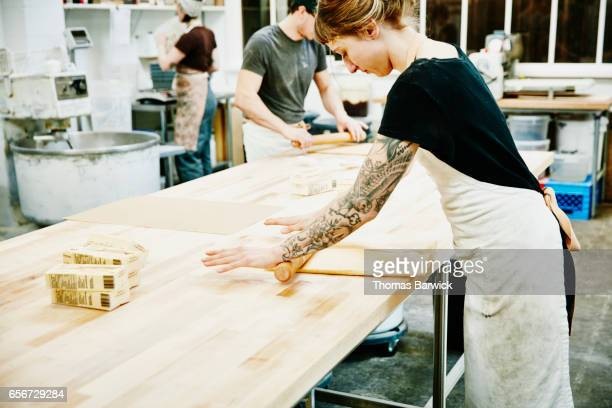 Bakers rolling butter for croissant dough at table in bakery