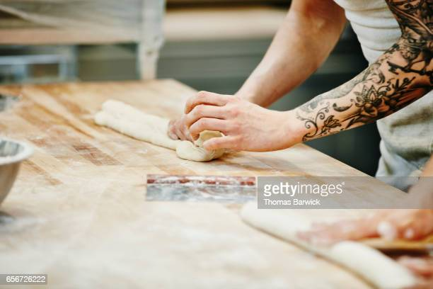 Bakers shaping dough for baguettes at table in bakery