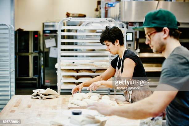 Bakers shaping dough for baguettes in commercial bakery