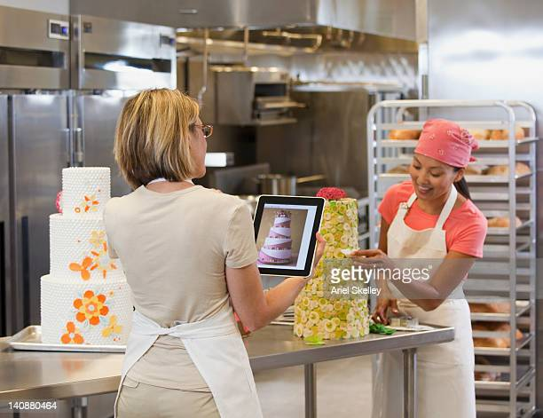Bakers using digital tablet to decorate cake in bakery