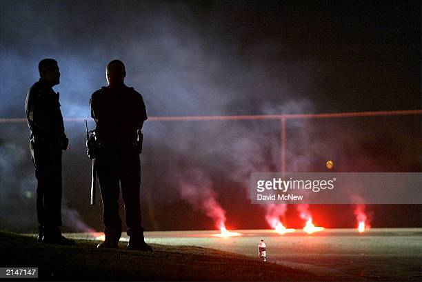 Bakersfield police officers stand by outside the house where five people including three children were murdered on July 8 2003 in Bakersfield...