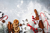 Bakery food background for cooking christmas baking with rolling pin, scattered flour and spices decorated with fir tree top view.