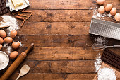 Bakery ingredients and tools over rustic wooden table. Dark and brown colors. Homemade style. Top view and space for text