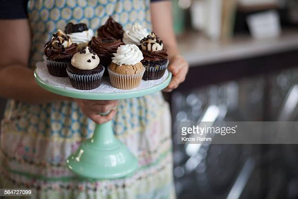 Bakery owner carrying tray of allergy-friendly cupcakes