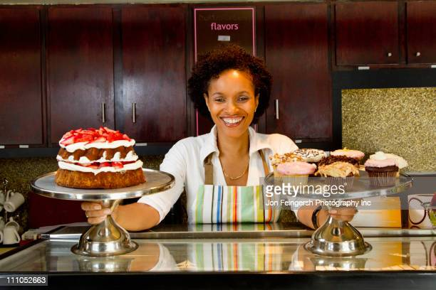 Bakery owner displaying baked goods
