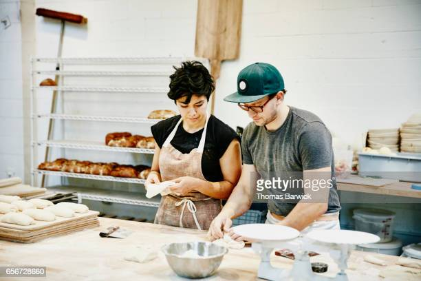 Bakery owner showing employee how to shape dough for baguettes