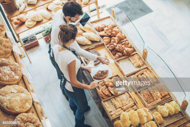 Bakery owners arranging the display in the bakery