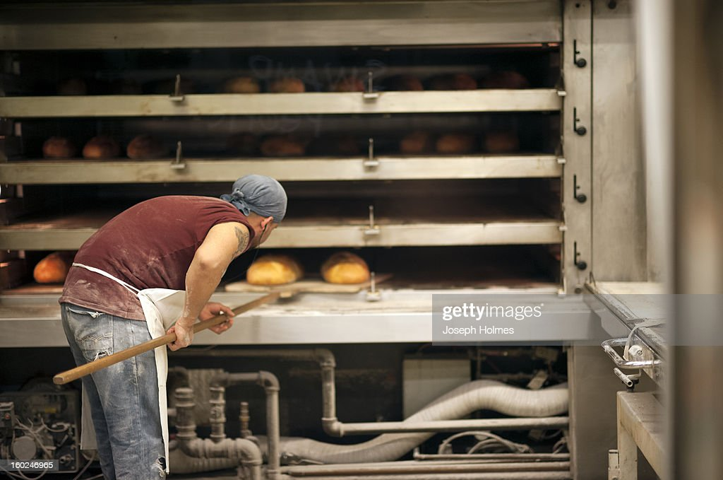 CONTENT] A bakery worker checks the bread in an oven at Amy's Bread, a commercial bakery in New York City's Chelsea Market.