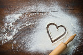 Baking background with the rolling pin, heart shape and flour on the wooden table. Copy space for text. Top view