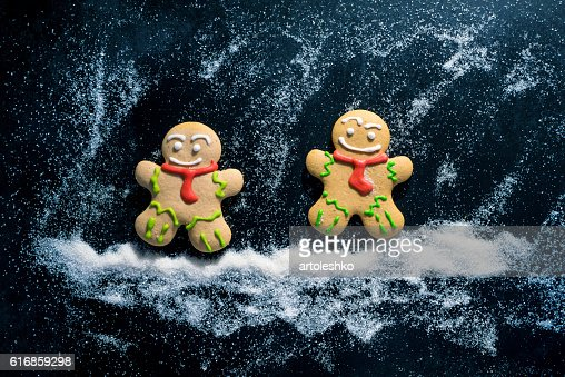 Baking Gingerbread Men for Christmas on dark table : Stock Photo