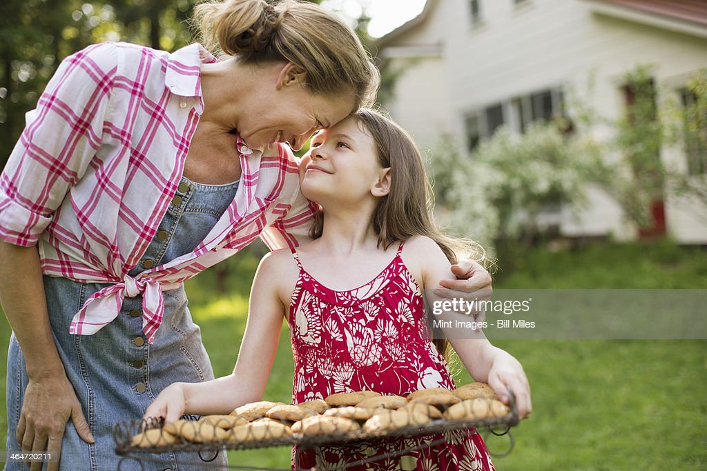 Baking homemade cookies. A young girl holding a tray of fresh baked cookies, and an adult woman leaning down to praise her.