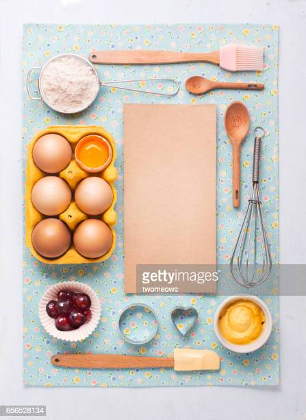 Baking ingredients and utensils on blue background.