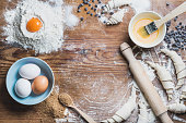 Baking ingredients for cooking croissants. Eggs, brown sugar, melted butter, flour, chocolate chips over rustic wooden background. Top view, copy space