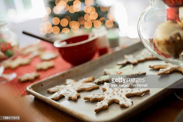 Baking tray of organic homemade Christmas cookies in the shapes of icicles and stars.