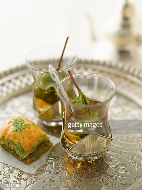 Baklava with peppermint tea on silver tray, close up