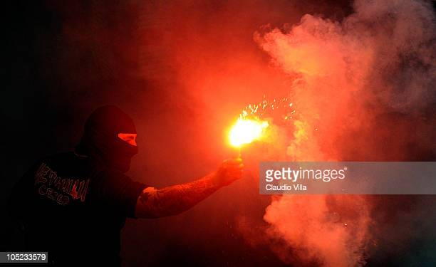 Balaclava clad Serbian fan Ivan Bogdanov gestures towards riot police during the Uefa Euro 2012 qualifying match between Italy and Serbia at Luigi...
