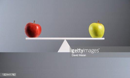 Balance between a red & a green apple. : Stock Photo