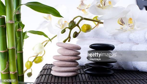 Massagem pedras equilibradas no tapete com toalhas de