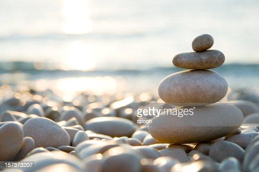 Equilibrio pietre su una spiaggia di ciottoli durante il tramonto.