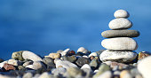 balancing stone tower against blue sea