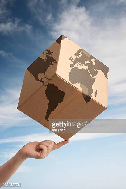 Balancing worldwide trade cardboard box and world map