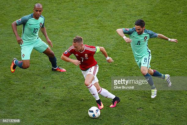 Balazs Dzsudzsak of Hungary competes for the ball against Joao Mario and Joao Moutinho of Portugal during the UEFA EURO 2016 Group F match between...