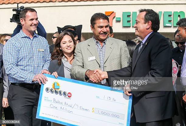 Balbir Atwal center owner of the California 7Eleven that sold one of the 3 Powerball winning tickets receives a $1 million check from Hugo Lopez...