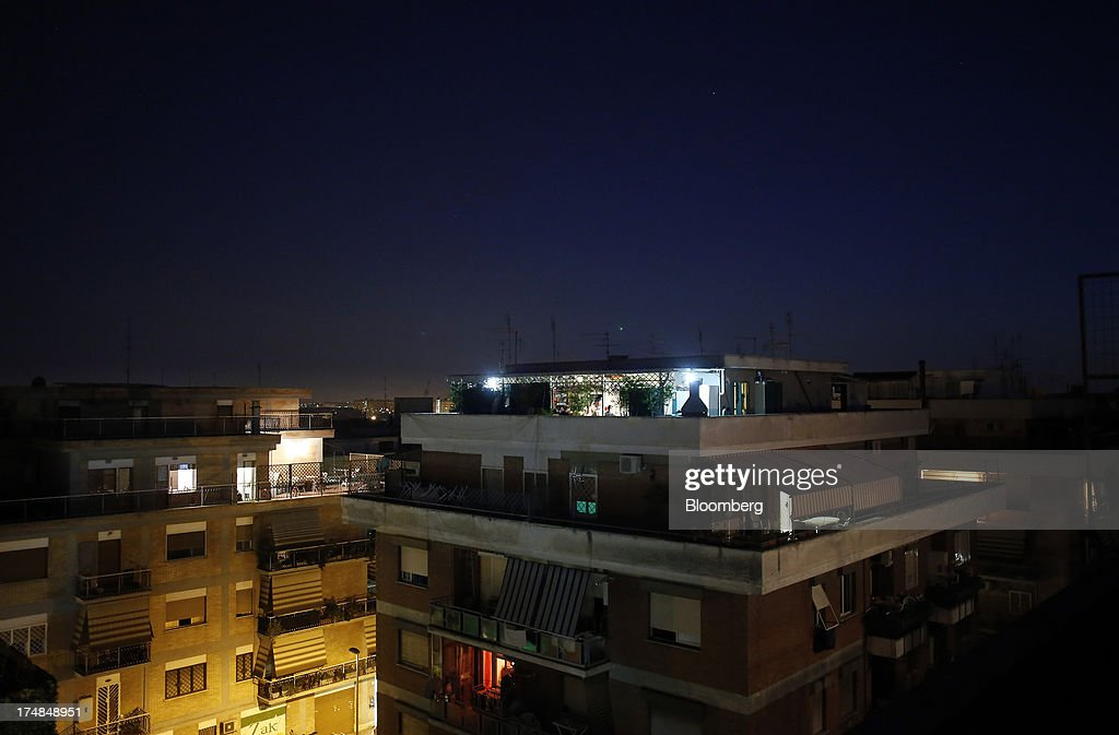 Balconies and roof terraces are illuminated at night on a residential apartment buildings in Rome, Italy, on Saturday, July 27, 2013. Italy's home prices are low enough to trigger an increase in purchases for the first time since 2006, though that won't lift values for at least two years, according to the Nomisma institute. Photographer: Alessia Pierdomenico/Bloomberg via Getty Images