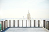 Balcony with railing and foggy New York city view with copy space. 3D Rendering