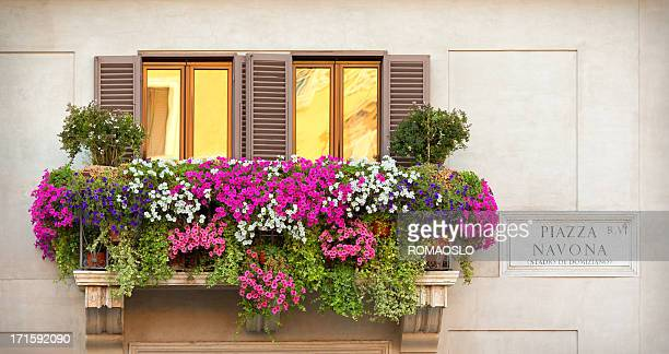 A balcony with multicolored flowers