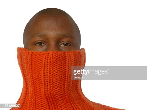 A bald African man hides his face in an orange sweater