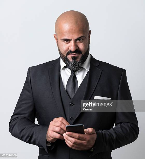 bald businessman holding smartphone looking at camera
