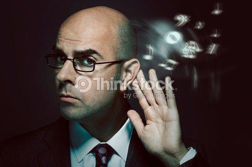 Bald businessman listening to music : Foto de stock
