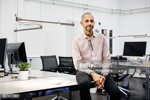 Bald businessman sitting on a desk